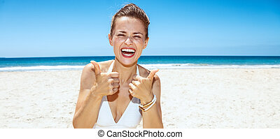Smiling woman in white swimsuit at sandy beach showing...