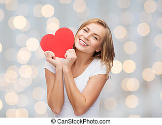 smiling woman in white t-shirt holding red heart -...