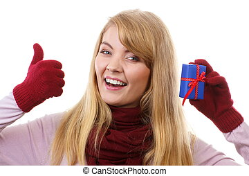 Smiling woman in woolen gloves with wrapped gift for Christmas showing thumbs up