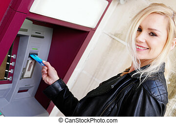 Close up Smiling Blond Woman Inserting a Card in an ATM While Looking at the Camera.