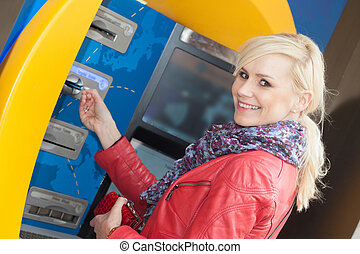 Smiling woman inserting her card in an ATM