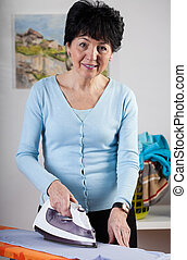 Smiling woman ironing