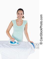 Smiling woman ironing