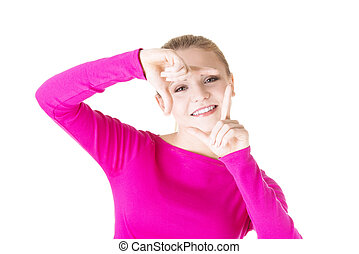 Smiling woman is showing frame by hands.