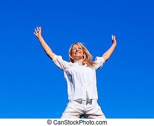 Smiling woman jumping against blue sky