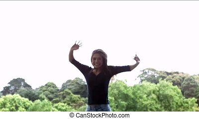 Smiling woman jumping in slow motion