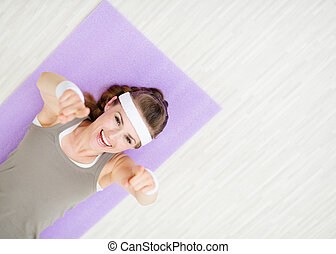Smiling woman laying on fitness mat and pointing on you