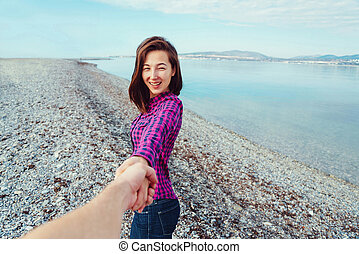 Smiling woman leading man on beach near the sea