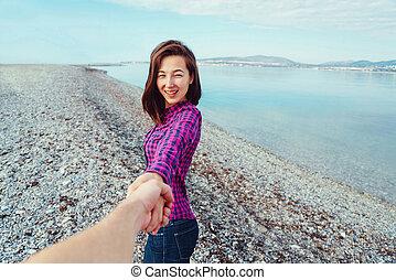 Smiling woman leading man on beach near the sea