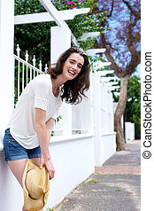 Smiling woman leaning against white wall