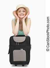 Smiling woman leaning on a suitcase while sitting
