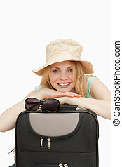 Smiling woman leaning on a suitcase