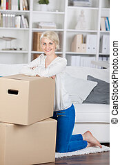 woman leaning on cardboard boxes at home