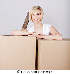 smiling woman leaning on cardboard boxes