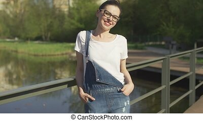 Smiling woman leaning on handrail above water