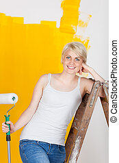 smiling woman leaning on ladder