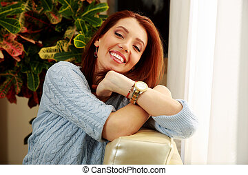 Smiling woman leaning on sofa at home