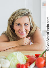 Smiling woman leaning on table
