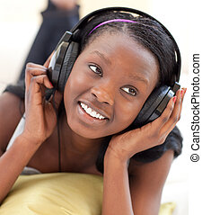 Smiling woman listening music lying on a sofa