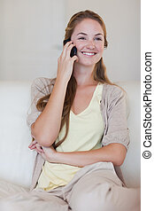 Smiling woman listening to caller on her cellphone