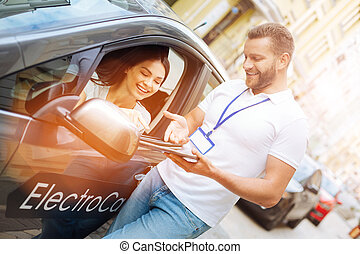 Smiling woman listening to car rental agency employee