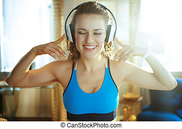 smiling woman listening to music with headphones at modern home