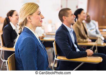 Smiling woman listening to speaker at business training