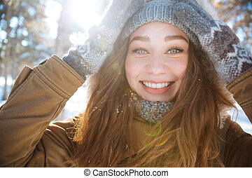 Smiling woman looking at camera in winter park