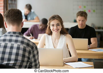 Smiling woman looking at camera sitting at desk
