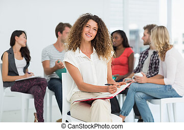 Smiling woman looking at camera while colleagues are talking behind her in creative office