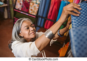 Smiling woman looking at cloth rolls in a fabric shop