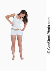 Smiling woman looking at her waist