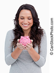 Smiling woman looking at piggy bank in her hands