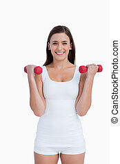 Smiling woman looking at the camera while holding dumbbells