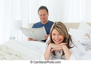 Smiling woman looking at the camera while her husband is reading at home