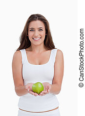 Smiling woman looking at the camera while holding an apple