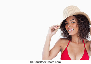 Smiling woman looking at the camera while holding her straw hat