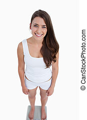 Smiling woman looking at the camera while standing on weighing scales