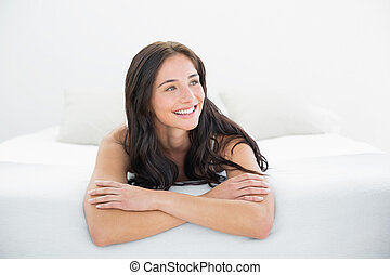 Smiling woman looking away in bed
