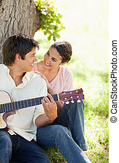 Smiling woman looking eye to eye with her friend who is holding a guitar as they both sit against a tree