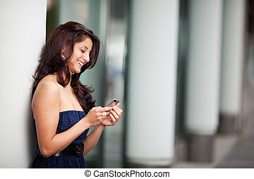 smiling woman looking on mobile phone
