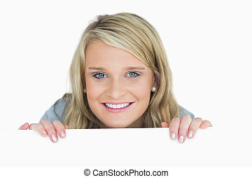 Smiling woman looking over poster - Smiling blonde woman...