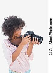 Smiling woman looking through digital camera