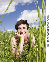 Smiling woman lying in the grass