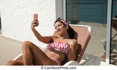 Smiling woman lying on deckchair making selfie on smartphone.
