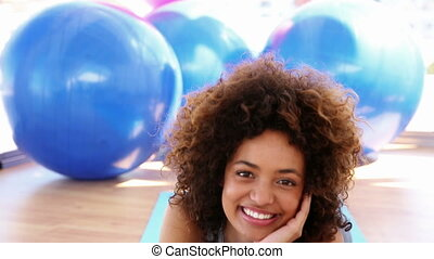 Smiling woman lying on exercise mat at the gym