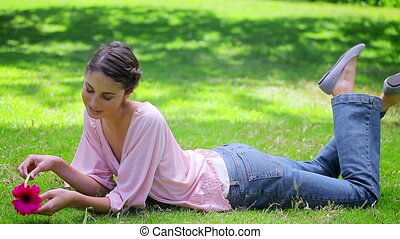 Smiling woman lying on the grass while holding a flower