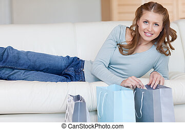 Smiling woman lying on the sofa next to her shopping