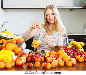 Smiling woman making fruits beverages