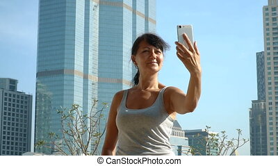 Smiling woman making selfie at the skyscraper background